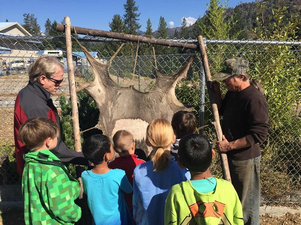 Students learning how to tan a deer hide